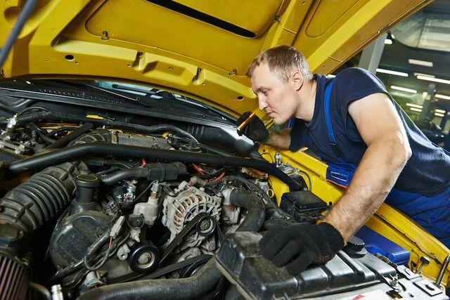 Автомеханик осматривает двигатель