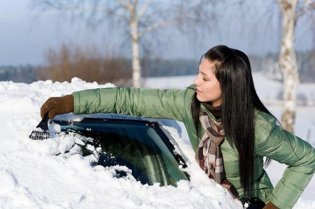 Женщина убирает снег с машины