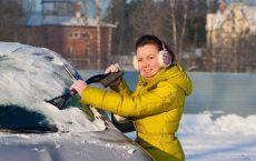 Девушка чистит от снега машину